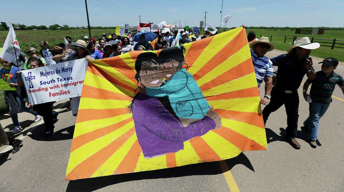 Marchers make their way along State Highway 85 on their way toward the the immigrant detention center to march and protest in Dilley, Texas on Saturday, May 2, 2015.