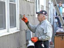 Don Blackwell, of New Fairfield, works at touching up around a window as he works with other volunteers from Saint Edwards Church, in New Fairfield, on a Woodlawn Drive home in Bethel, as part of the 28th Annual HomeFront Day, a volunteer home repair campaign that will revitalize 70 homes this year,  on Saturday, May 2, 2015, in Bethel, Conn.
