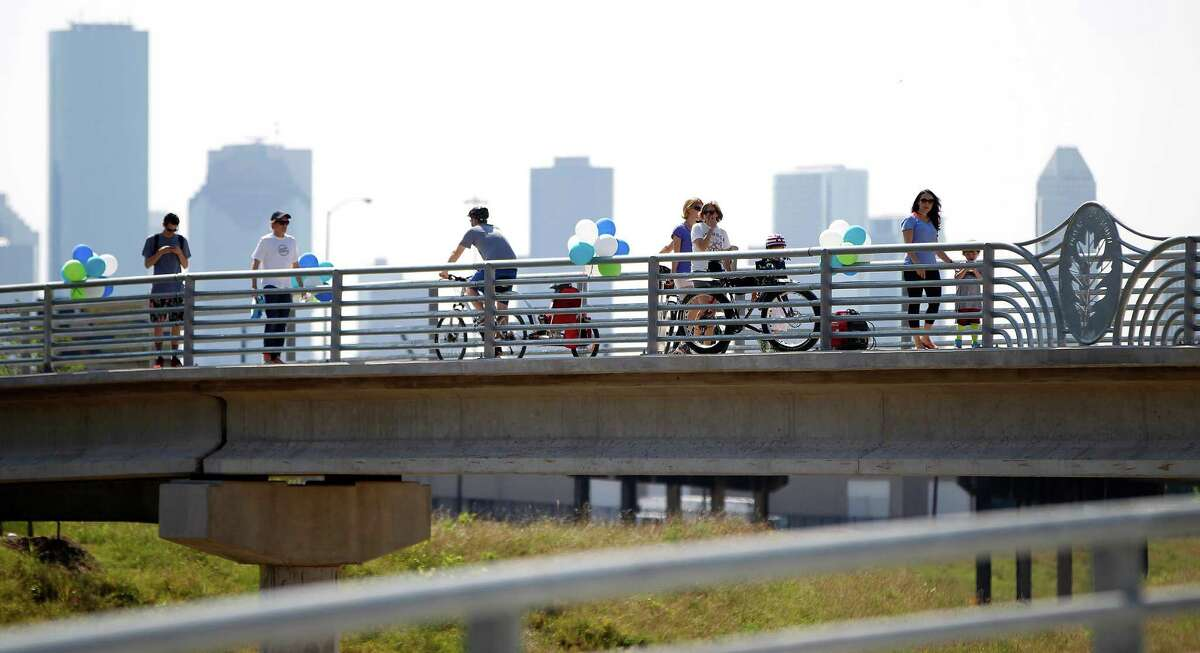 People walk and ride bikes on the new White Oak Bayou greenway bridge and trails, West of Heights Trail during the Bridge Bash festivities on Saturday, May 2, 2015, in Houston. The Houston Parks Board, Memorial Heights Redevelopment Authority and Tax Increment Reinvestment Zone (TIRZ) 5, and the City of Houston will host a âÄúBridge BashâÄù to celebrate the completion of a new segment of White Oak Bayou Greenway.The new bridge replaces the former MKT Railroad Bridge, also known as the âÄúBBQ BridgeâÄù between Shepherd Drive and Moy Street.