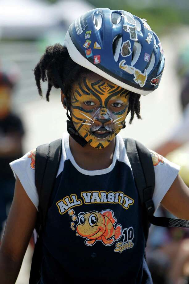 Yuriko White, 9, with her face painted, roller skates during Bridge Bash ceremonies at the new White Oak Bayou greenway bridge and trails, West of Heights Trail on Saturday, May 2, 2015, in Houston.  The Houston Parks Board, Memorial Heights Redevelopment Authority and Tax Increment Reinvestment Zone (TIRZ) 5, and the City of Houston will host a âÄúBridge BashâÄù to celebrate the completion of a new segment of White Oak Bayou Greenway.The new bridge replaces the former MKT Railroad Bridge, also known as the âÄúBBQ BridgeâÄù between Shepherd Drive and Moy Street. Photo: Karen Warren, Houston Chronicle / © 2015 Houston Chronicle