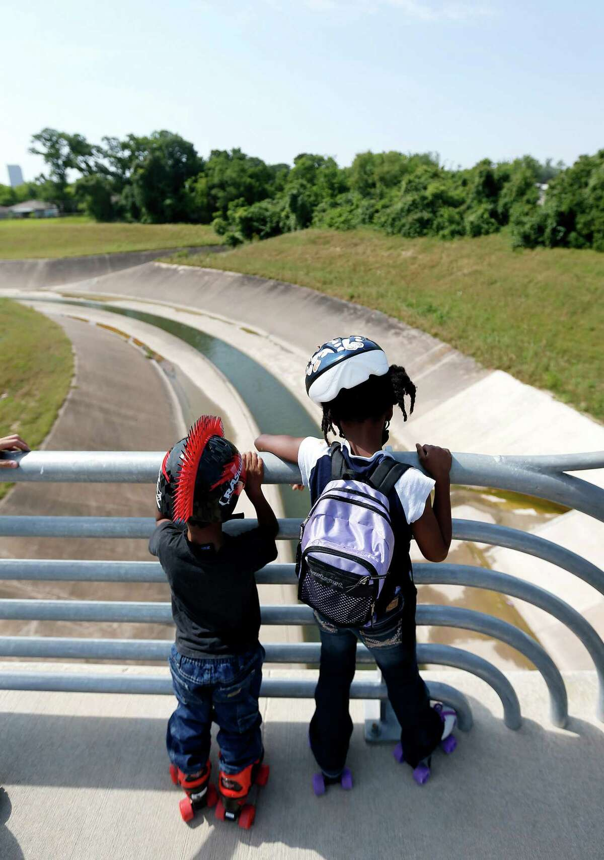 Sion White, 5, and Yuriko White, 9, watch the waters flow in the White Oak Bayou during Bridge Bash ceremonies at the new White Oak Bayou greenway bridge and trails, West of Heights Trail on Saturday, May 2, 2015, in Houston. The Houston Parks Board, Memorial Heights Redevelopment Authority and Tax Increment Reinvestment Zone (TIRZ) 5, and the City of Houston will host a âÄúBridge BashâÄù to celebrate the completion of a new segment of White Oak Bayou Greenway.The new bridge replaces the former MKT Railroad Bridge, also known as the âÄúBBQ BridgeâÄù between Shepherd Drive and Moy Street.