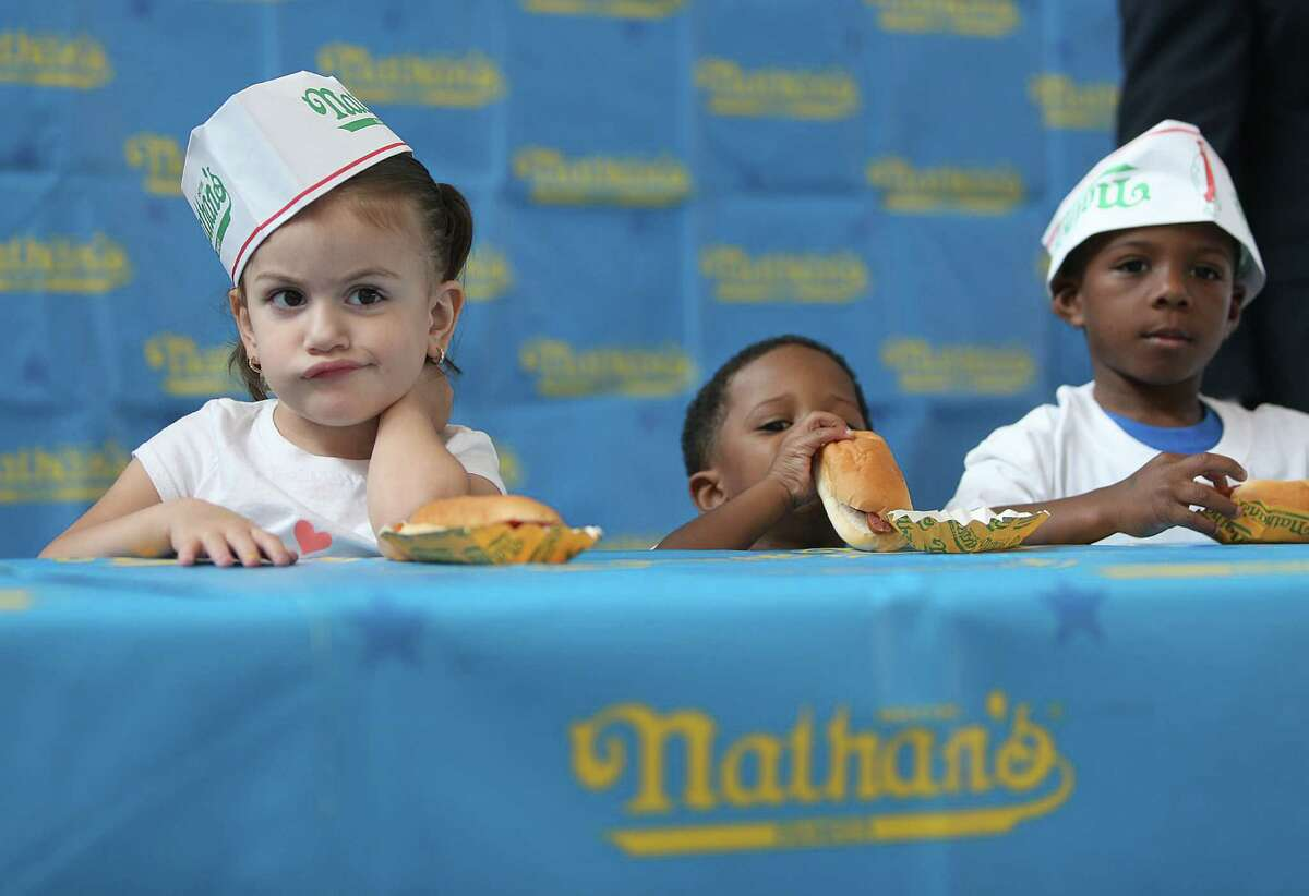 Helina Zubizarreta, 3, reacts to the rules of the contest: no speed eating, neat eating only, competing with manners while Dylan Harvey, 2, (center) gets a head start and brother Danny Harvey, 4, waits for start during the kids hot dog eating contest on Saturday, May 2, 2015, in Houston. Major League Eating and Memorial City host the regional qualifier. The top adult male and female finishers will qualify for a seat at the Nathan's Famous Fourth of July International Hot Dog-Eating Contest.