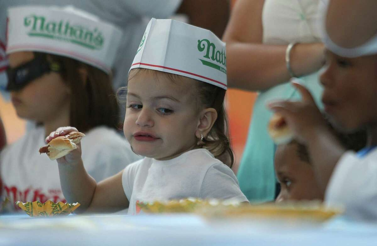(Left) Helina Zubizarreta, 3, looks over at the competition during the kids hot dog eating contest on Saturday, May 2, 2015, in Houston. Major League Eating and Memorial City host the regional qualifier. The top adult male and female finishers will qualify for a seat at the Nathan's Famous Fourth of July International Hot Dog-Eating Contest.