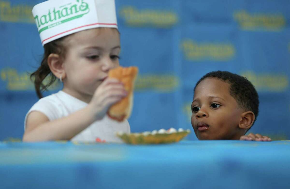 (Left) Helina Zubizarreta, 3, neatly eats her hot dog while Dylan Harvey looks over at the competition during the kids hot dog eating contest on Saturday, May 2, 2015, in Houston. Major League Eating and Memorial City host the regional qualifier. The top adult male and female finishers will qualify for a seat at the Nathan's Famous Fourth of July International Hot Dog-Eating Contest.