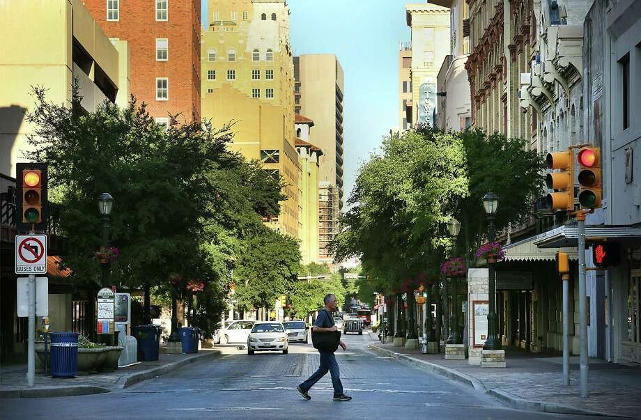 A man walks across Houston St. at Alamo St., as the early morning sun warms the city. The historic Houston St. may be experiencing some significant changes that could truly revive downtown. Photo: Bob Owen /San Antonio Express-News / San Antonio Express-News