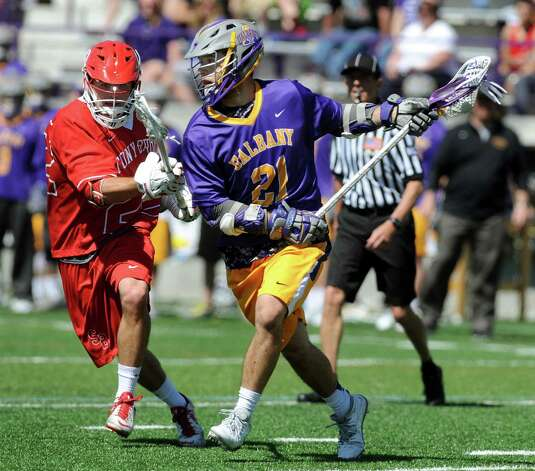 UAlbany's Seth Oakes, right, carries the ball as Stony Brook's Lucas Rock defends in the America East Conference championship lacrosse game on Saturday, May 2, 2015, at Bob Ford Field in Albany, N.Y. (Cindy Schultz / Times Union) Photo: Cindy Schultz / 00031627A