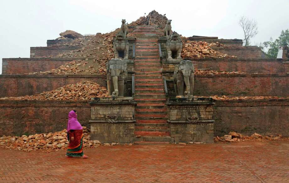 In this Thursday, April 30, 2015 photo, a Nepalese woman walks by rubbles at Bhaktapur Durbar Square, a UNESCO World Heritage Site, on the outskirts of Kathmandu, Nepal.  Built between the 12th and 18th centuries, the square was traditionally used for coronation ceremonies  and religious festivals. (AP Photo/Manish Swarup) Photo: Manish Swarup, STF / Associated Press / AP