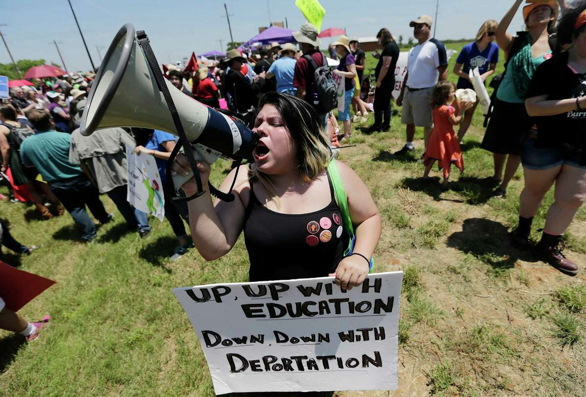 Chasity Valerio yells into a bull horn during the immigrant detention center march and protest in Dilley, Texas on Saturday, May 2, 2015. (Kin Man Hui/San Antonio Express-News)