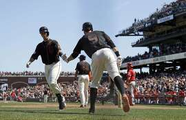 San Francisco Giants' Buster Posey, left, celebrates his solo home run with teammate Brandon Belt (9) during the seventh inning of a baseball game on Saturday, May 2, 2015, in San Francisco. (AP Photo/Marcio Jose Sanchez)