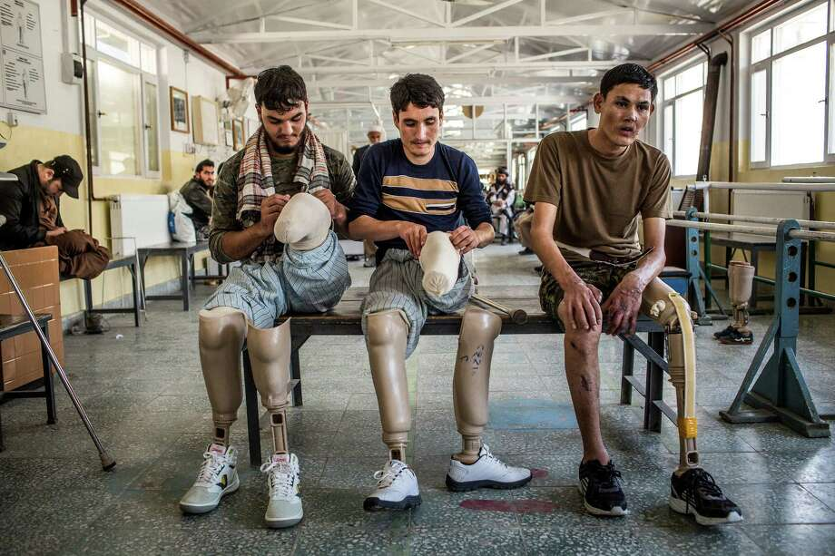 Afghan National Army soldiers who have had injuries and amputations adjust their prostheses between sessions at a therapy center. Photo: Bryan Denton / New York Times / NYTNS