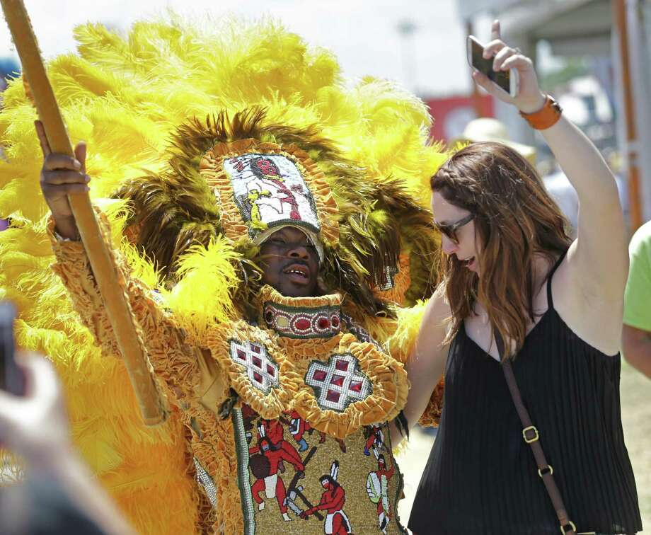 A member of the New Orleans Mardi Gras Indian Rhythm Section, with the Algiers Warriors and Golden Comanche Mardi Gras Indians, dances with a festival-goer in a second line parade at the New Orleans Jazz and Heritage Festival in New Orleans, Friday, May 1, 2015. Photo: Gerald Herbert, Associated Press / AP