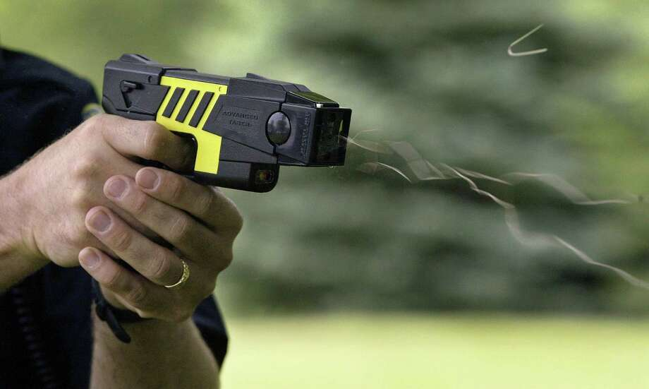 The use of the is M26 Advanced Taser is demonstrated by the Marion Police Department, Tuesday, June 7, 2004, in Marion, Iowa. The non-lethal force weapon uses Electro-Muscular Disruption to override the central nervous system. A 50,000 volt, 26-watt charge causes an uncontrollable contraction of muscle tissue. A normal hit from the Taser lasts for five seconds. The time allows officers to subdue the subject before that person can recover. (AP Photo/The Gazette, Jim Slosiarek) Photo: JIM SLOSIAREK / 2004 AP