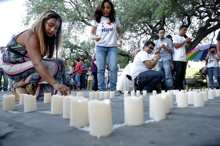 Candles are placed on an outline shaped like Nepal as the Nepalese community remembers the earthquake victims. Photo: Tom Reel /San Antonio Express-News