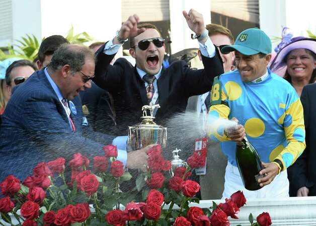 Jockey Victor Espinoza sprays champagne over the winner's circle crowd after winning  the 141st Kentucky Derby on American Pharaoh  May 2, 2015 at Churchill Downs in Louisville, Kentucky.      (Skip Dickstein/Times Union) Photo: SKIP DICKSTEIN