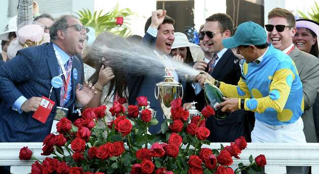 Jockey Victor Espinoza sprays champagne at owner Ahmed Zayat, left in the winner's circle after winning  the 141st Kentucky Derby on American Pharaoh  May 2, 2015 at Churchill Downs in Louisville, Kentucky.      (Skip Dickstein/Times Union) Photo: SKIP DICKSTEIN