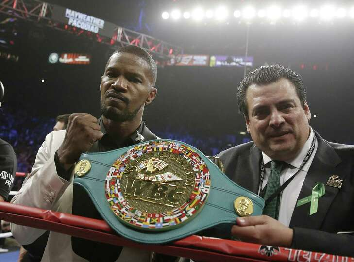 Actor Jamie Foxx, left, poses with the champion's belt after singing the national anthem before the