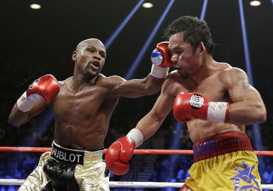 Floyd Mayweather (left) was stripped of the WBO welterweight title he won from Manny Pacquiao during their May 2 fight in Las Vegas. Photo: Isaac Brekken, Associated Press