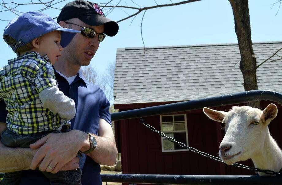 Matt Smith of Westport and son, Alex, 15 months, meet Daisy the goat during Wakeman Town Farm's GreenDay celebration. Photo: Jarret Liotta / Westport News