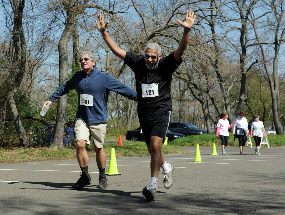 Michael Spilo, left, and Sunil Hirani, of Greenwich, joke around while crossing the finish line in the CancerCare Walk/Run for Hope at Greewich Point Park in Old Greenwich, Conn. Sunday, May 3, 2015. More than 250 participated in the third annual event that celebrates survivors, those facing cancer and those lost to cancer.