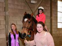 Volunteers Carly Hohorst, left, and Cayla Noble, right, lead one of the ponies with Jordan Silva,10, for her ride. The Second Company Governor's Horse Guard hosted a Pony Rides for a Purpose Fundraiser on Sunday May 3, 2015. All proceeds from the event will go to The Jessica Rekos Foundation. The Foundation provides children, who would not otherwise have the opportunity, with a year long riding lesson scholarship. Jessica Rekos was one of the students killed at Sandy Hook.