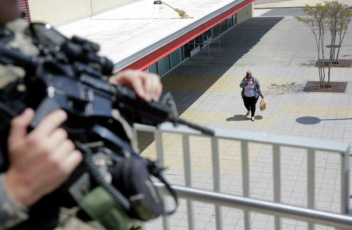 A shopper walks outside of the Mondawmin Mall as a member of the Maryland National Guard patrols, Sunday, May 3, 2015, in Baltimore. The mall opened for the first time since unrest took place on the property Monday.Latest from AP: Baltimore lifts curfew after days of tension