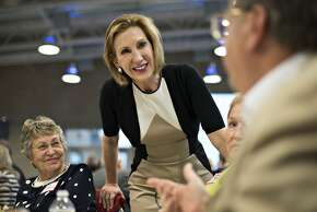 """Carly Fiorina, former chief executive officer of Hewlett-Packard Co. and likely Republican presidential candidate for 2016, center, speaks with attendees during the Johnson County Chili Supper at Clear Creek Amana High School in Tiffin, Iowa, U.S., on Friday, April 24, 2015. Fiorina scuttled what little suspense remained about her forthcoming presidential campaign this week, telling an Iowa audience that she would jump into the race """"within a couple weeks,"""" the Des Moines Register reported. Photographer: Daniel Acker/Bloomberg *** Local Caption *** Carly Fiorina"""