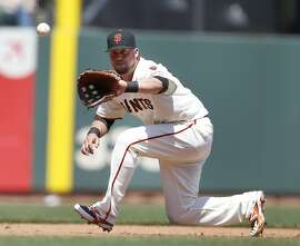 San Francisco Giants third baseman Casey McGehee catches a line drive hit by Los Angeles Angels' Johnny Giavotella during the fifth inning of a baseball game on Sunday, May 3, 2015, in San Francisco. (AP Photo/Tony Avelar)