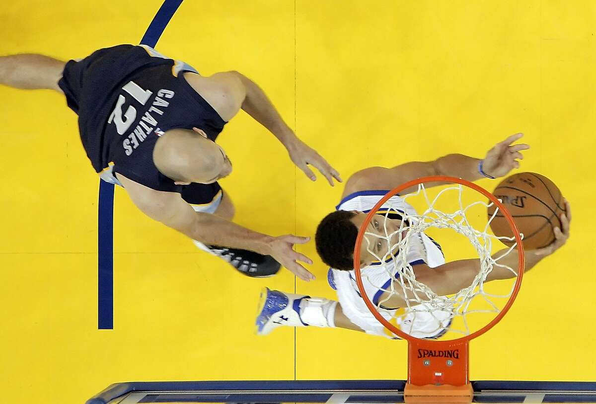 Stephen Curry (30) attempts a reverse layup with Nick Calathes (12 in pursuit during the first half. The Golden State Warriors played the Memphis Grizzlies at Oracle Arena in Oakland, Calif., in Game 1 of the Western Conference Semifinals on Sunday, May 3, 2015.