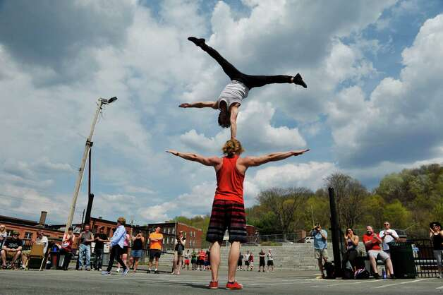 Members of Light Up Troy Productions, Cesar Mispelon balances on the head of Julius Bitterling as they perform at the 7th annual Stick it to Hunger stick ball tournament on Sunday, May 3, 2015, in Troy, N.Y.  The event raises money and food for area food pantries.  Organizers said that the event has raised over $60,000 since it started and that they hope to raise $15,000 this year.  (Paul Buckowski / Times Union) Photo: PAUL BUCKOWSKI / 00031670A