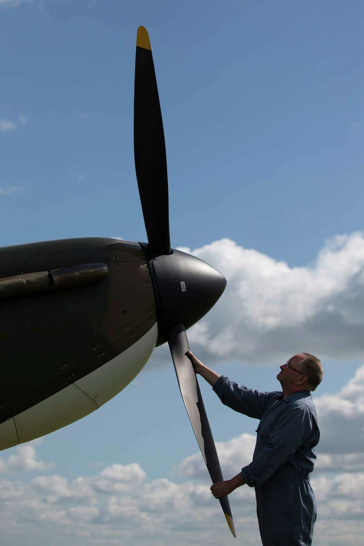 A technician poses for a photograph with the propeller of a restored Vickers Supermarine Spitfire Mk.1A on April 27, 2015 at Imperial War Museum Duxford in Cambridge, England. The Spitfire, one of the last of its kind remaining, is due to be auctioned for charity on 9 July 2015 and is expected to fetch between 1.5 - 2.5 million GBP (2.25 - 3.8 million USD)Go here for details of the auction.