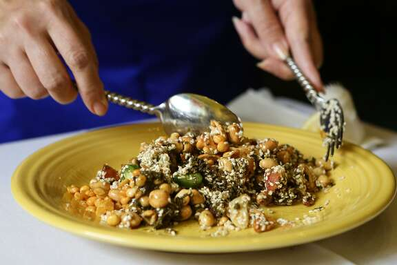 Owner Sherry Dung mixes a traditional Burmese tea leaf salad at Mandalay restaurant in San Francisco, Calif., on Sunday, May 3, 2015.