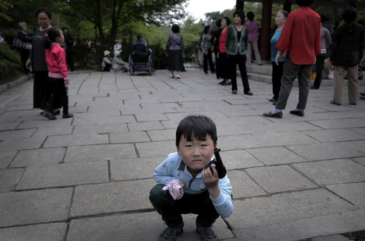 A North Korean boy plays with a toy pistol as elderly people gather around a gazebo, Sunday, May 3, 2015, at the Moranbong, or Moran Hill, in Pyongyang, North Korea.