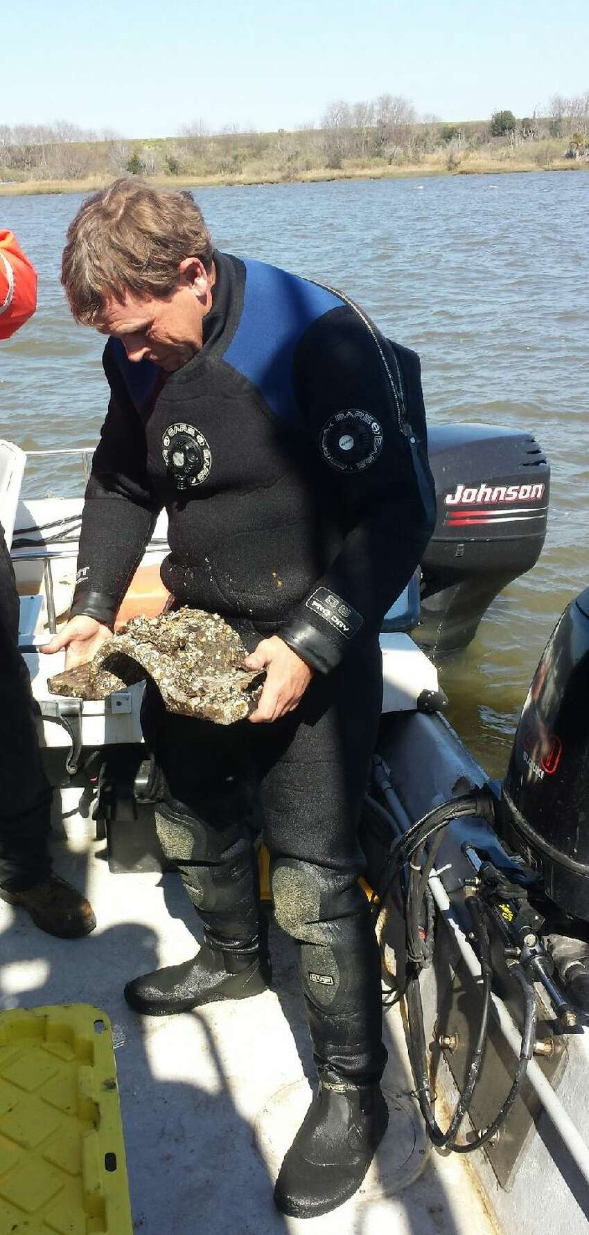 Marine archaeologist Jim Duff holds a gun carriage cap square discovered while recovering artifacts from the CSS Georgia.