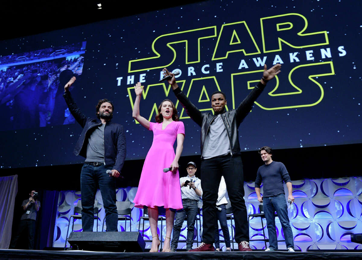 """Oscar Isaac, Daisy Ridley, John Boyega of """"Star Wars: The Force Awakens"""" and back row (L-R) writer, director and producer J.J. Abrams, producer Kathleen Kennedy and host Anthony Breznican, Entertainment Weekly reporter, acknowledge fans at the kick-off event during Disney's Star Wars Celebration 2015 at the Anaheim Convention Center April 16, 2015."""