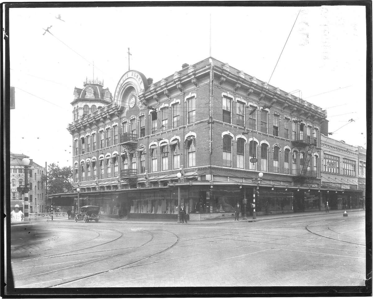 An oblique view of the George Dullnig Building, looking northwest at the corner of Alamo and Commerce Streets. The edge of the Royalty Coin/Clifford Building is visible on the far left.