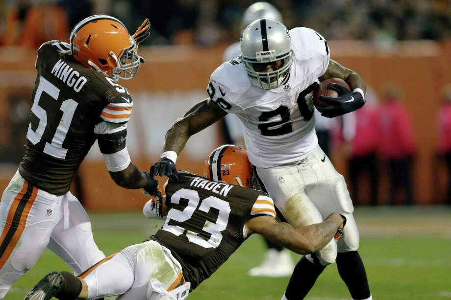 Oakland Raiders running back Darren McFadden is stopped for a loss by Cleveland Browns cornerback Joe Haden (23) and outside linebacker Barkevious Mingo (51) in the third quarter in Cleveland on Oct. 26, 2014. Photo: Tony Dejak /Associated Press / AP