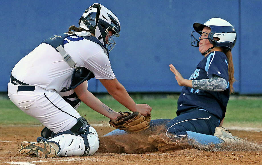 Smithson Valley catcher Kat Mathys tags out Taylor Drury of Johnson at the plate during the first round of the 2014 softball playoffs at the SAISD Spring Sports Complex. Photo: Tom Reel /San Antonio Express-News