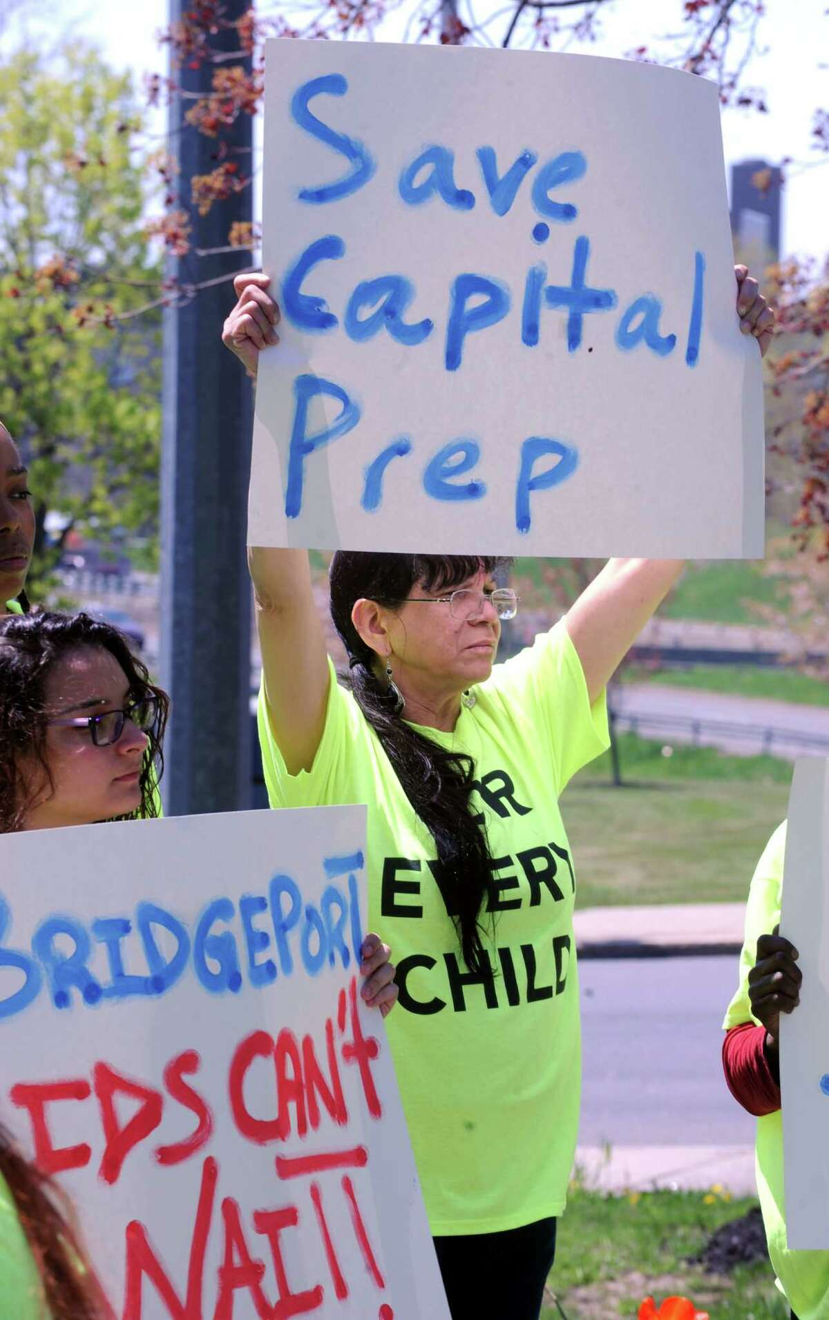 Elisa Martinez, a student at Bridge Academy, and Diana Toro, a grandmother to five students, held up signs as they rallied for restored state funding for a new charter school in City Hall Park in Bridgeport, Conn. on Monday, May 5, 2015.