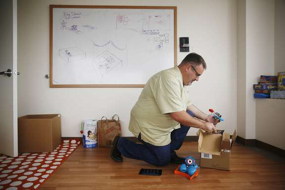 Ned Ward, vice president marketing, removes Dash and Dot and accessories from a box to display them in a testing room at Wonder Workshop on Monday, May 4, 2015 in San Mateo, Calif.