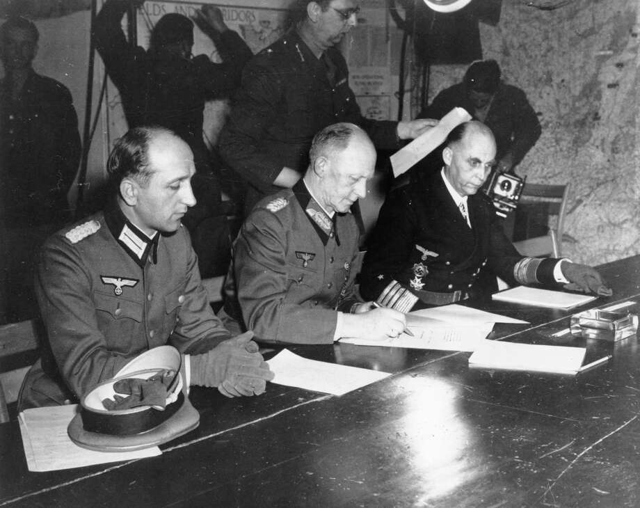General Alfred Jodl, center, signs the unconditional surrender of all armed German forces imposed by the Allied Powers, at Supreme Commander Eisenhowers headquarters in Rheims, France, on May 7, 1945. He is flanked by General Wilhelm Oxenius, Commander of the German Luftwaffe, left, and General Admiral and Commander in Chief of the German fleet, Hans-Georg von Friedeburg, right. Photo: File Photo / AP1945