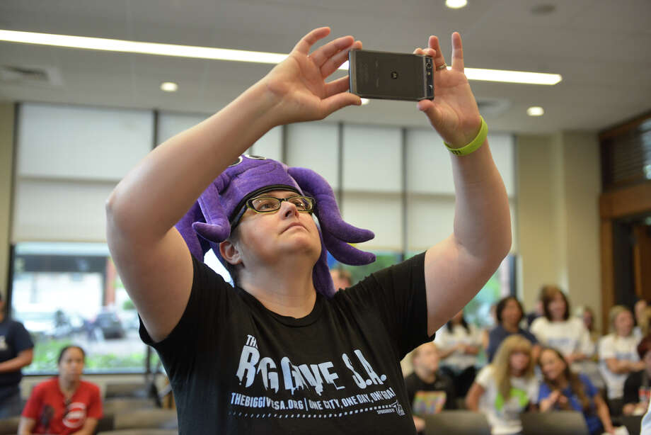 Heather C. Diehl, San Antonio Area Foundation donor relations officer-engagement, wears a purple octapuss hat while taking pictures during a press conference pep rally for the Big Give SA. Photo: Robin Jerstad / San Antonio Express-News