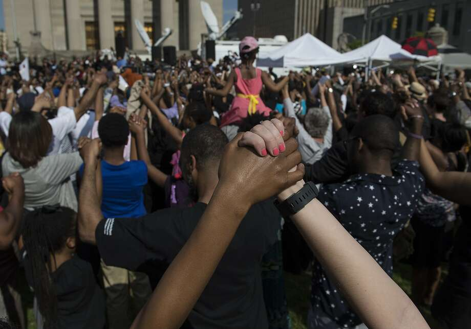 TOPSHOTS People pray a rally in front of City Hall in Baltimore, Maryland, on May 3, 2015 calling for peace following widespread riots. The riots stemmed from protests over the death of Freddie Gray, 25, who suffered a serious spinal injury while in the back of a police van on April 12.  AFP PHOTO/NICHOLAS KAMMNICHOLAS KAMM/AFP/Getty Images Photo: Nicholas Kamm, AFP / Getty Images