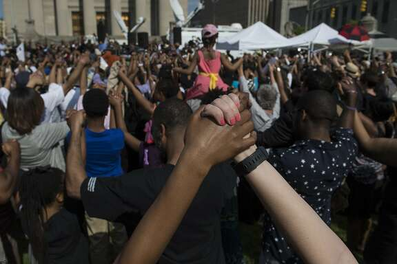 TOPSHOTS People pray a rally in front of City Hall in Baltimore, Maryland, on May 3, 2015 calling for peace following widespread riots. The riots stemmed from protests over the death of Freddie Gray, 25, who suffered a serious spinal injury while in the back of a police van on April 12.  AFP PHOTO/NICHOLAS KAMMNICHOLAS KAMM/AFP/Getty Images