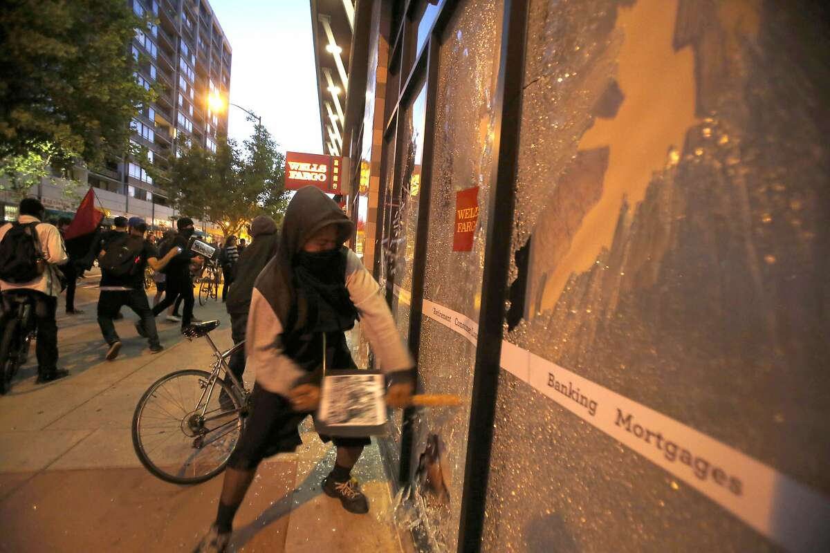 Demonstrators with their faces covered break windows at a Wells Fargo bank during one of the May Day protests in Oakland, Calif., on Friday, May 1, 2015. Oakland's mayor and some business owners called for tougher action Saturday after what police said was some of the heaviest damage yet in peaceful public marches in the San Francisco Bay city that have turned violent. (Ray Chavez/The Oakland Tribune via AP) MANDATORY CREDIT