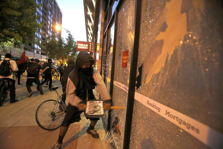 Demonstrators with their faces covered break windows at a Wells Fargo bank during one of the May Day protests in Oakland, Calif., on Friday, May 1, 2015. Oakland's mayor and some business owners called for tougher action Saturday after what police said was some of the heaviest damage yet in peaceful public marches in the San Francisco Bay city that have turned violent.  (Ray Chavez/The Oakland Tribune via AP) MANDATORY CREDIT Photo: Ray Chavez, Associated Press