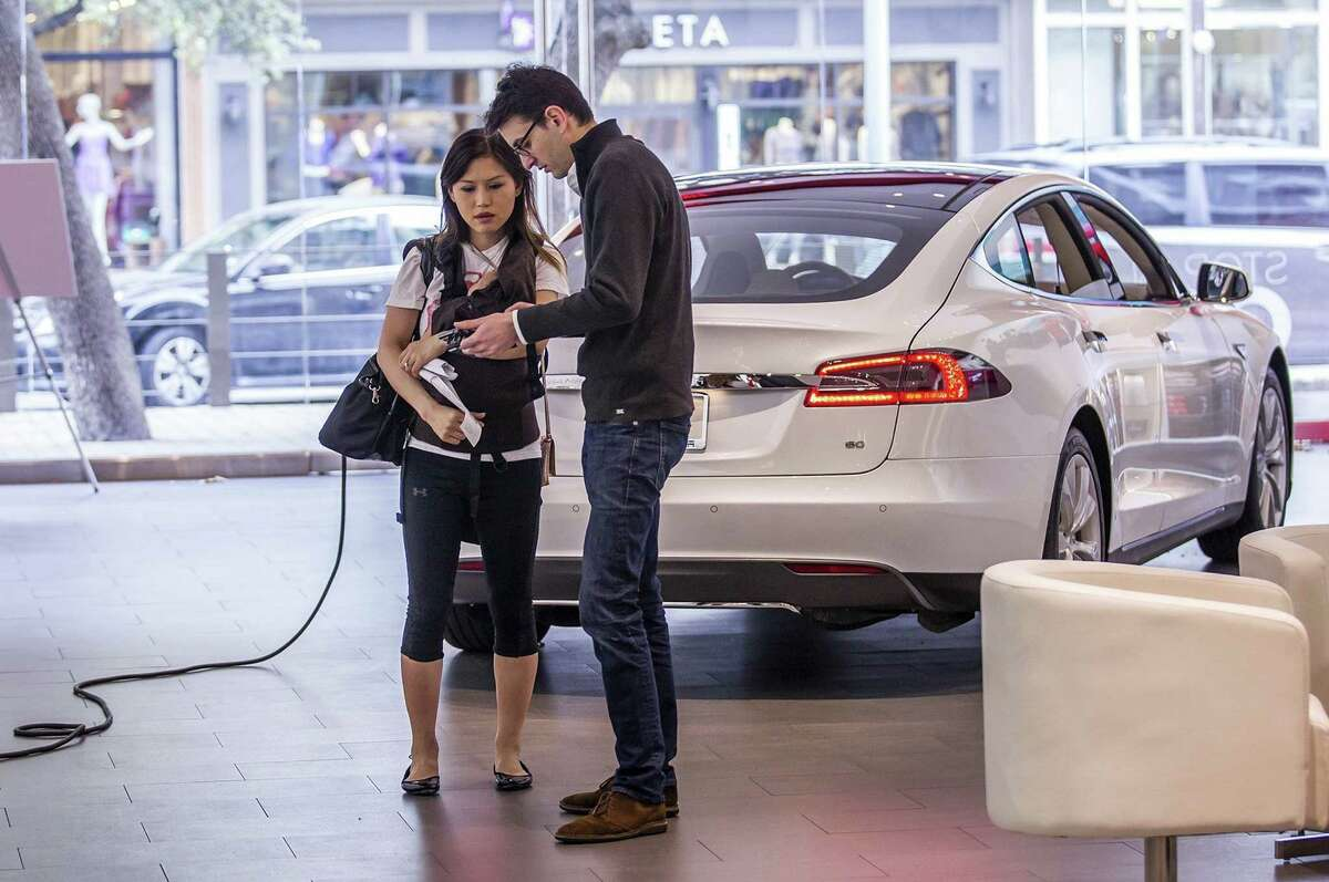Betty Lange holds son Jackson, 2 months, as Tesla product specialist Kevin Stanley tells her how the electric car works at The Domain in Austin. For now, the only way for a resident of Texas to get a Tesla is online or in another state. Legislative bills to change that aren't making much progress this session.