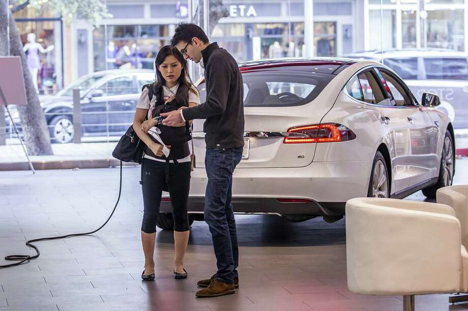 Betty Lange holds son Jackson as Tesla product specialist Kevin Stanley tells her how the electric car works at The Domain in Austin.   Photo: Ricardo Brazziell /Austin American-Statesman / Austin American-Statesman