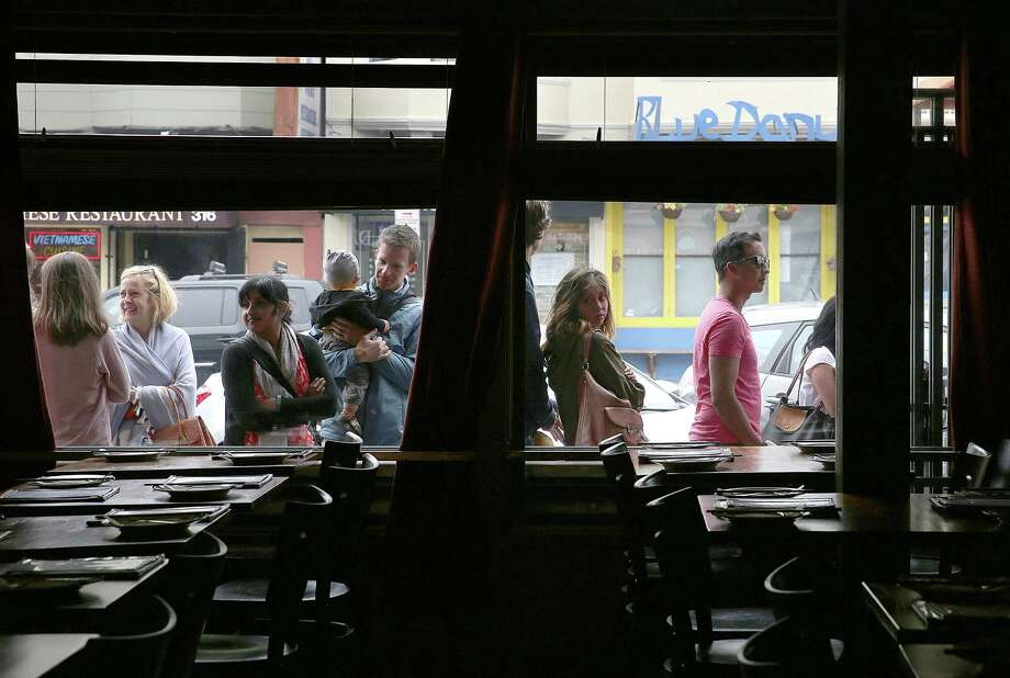 A line of diners wait for Burma Superstar to open for dinner in San Francisco — a far cry from the restaurant's struggle before owners Joycelyn Lee and Desmond Htunlin took over in 2001. Photo: Liz Hafalia / The Chronicle / ONLINE_YES