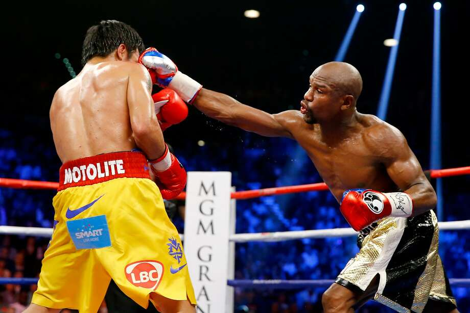 LAS VEGAS, NV - MAY 02:  Floyd Mayweather Jr. throws a right at Manny Pacquiao during their welterweight unification championship bout on May 2, 2015 at MGM Grand Garden Arena in Las Vegas, Nevada.  (Photo by Al Bello/Getty Images) *** BESTPIX *** Photo: Al Bello