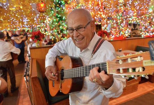 Mariachi musician Juan Aguilar plays his guitar in December 2013 at Mi Tierra in Market Square. Photo: San Antonio Express-News / File Photo / San Antonio Express-News